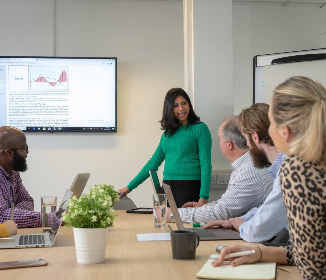 Group of people in boardroom looking at screen